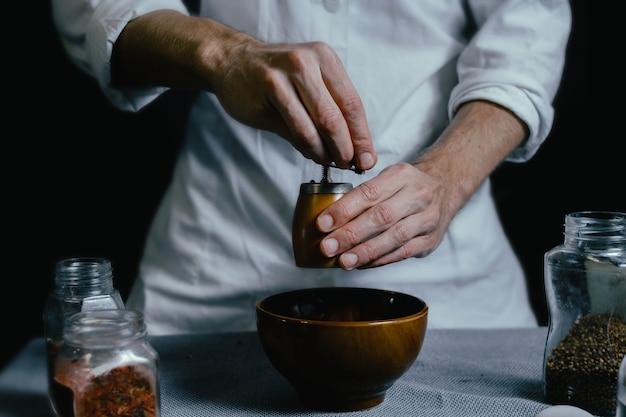 Lo chef macina le spezie in un mulino a mano