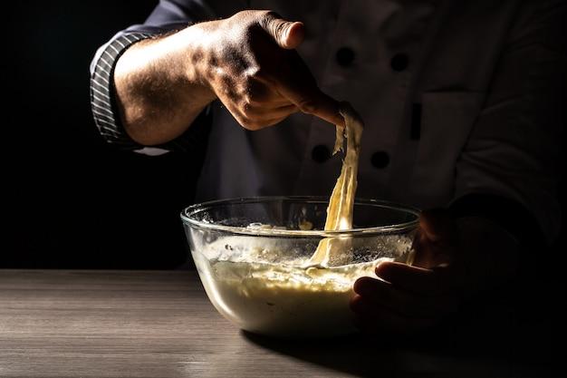 Mani del cuoco unico che cucinano pasta su fondo di legno scuro