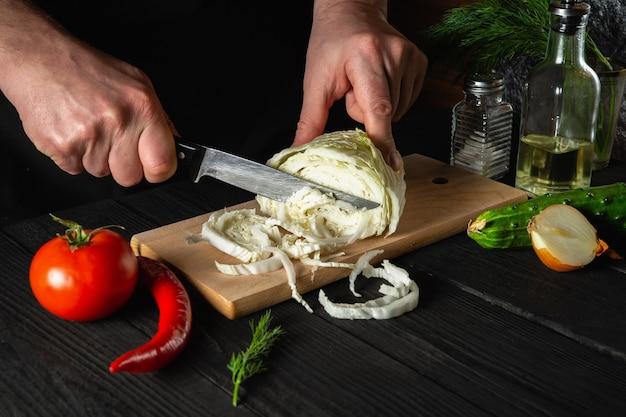 Mani dello chef che tagliano cavolo cinese fresco e verdure per insalata