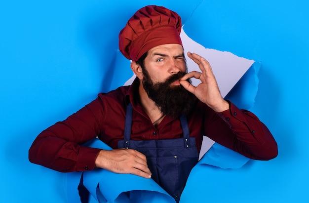 Chef in cappello e grembiule con segno perfetto. lo chef professionista mostra il segno per delizioso.