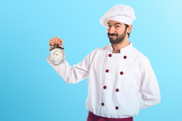 Chef in possesso di un orologio su sfondo bianco su sfondo colorato