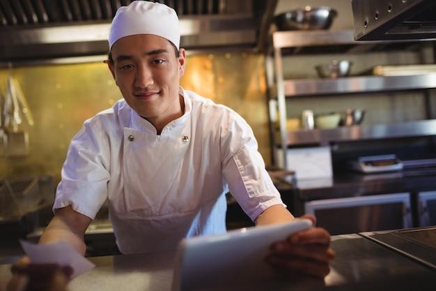 Chef in possesso di tavoletta digitale e un elenco di ordini in cucina