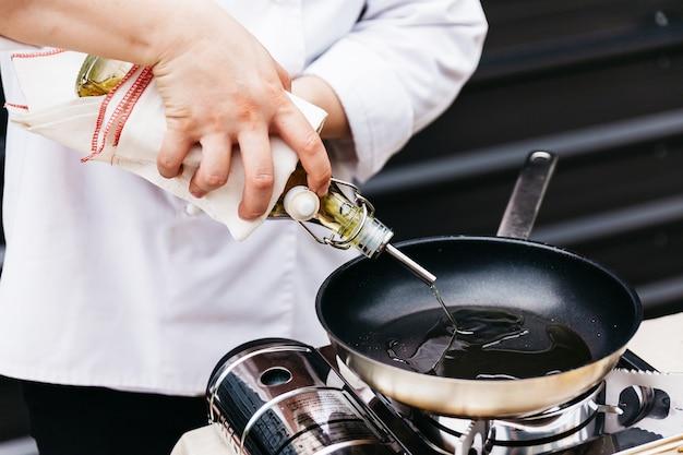 Chef tenendo una bottiglia di olio d'oliva che si avvolge con tessuto mentre versa l'olio d'oliva in una padella calda.