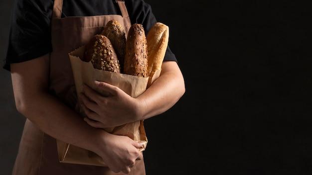 Cuoco unico che tiene il sacchetto di carta con il pane