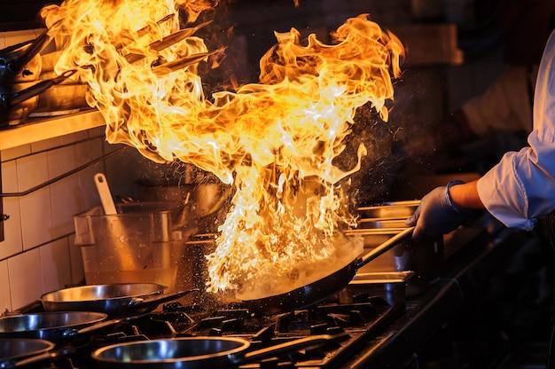 Lo chef sta mescolando le verdure nel wok sul fuoco aperto