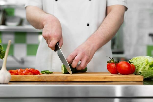 Lo chef in cucina taglia verdure fresche e deliziose per un'insalata di verdure