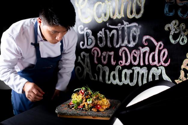 Chef cercando il suo piatto pronto per il cliente