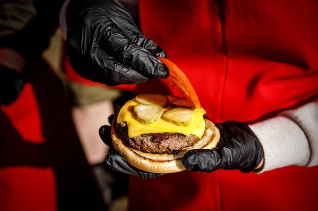 Lo chef prepara un hamburger con guanti neri. raccoglie gli ingredienti