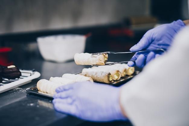 Lo chef prepara i biscotti sul tavolo da lavoro della panetteria.