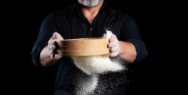 Lo chef un uomo in uniforme nera tiene tra le mani un setaccio di legno rotondo e setaccia la farina di grano bianco su sfondo nero, le particelle volano in diverse direzioni