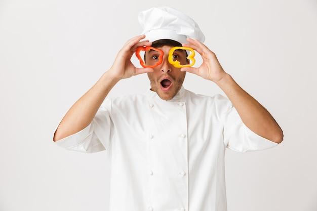 Uomo del cuoco unico isolato sulla parete bianca coning occhi con paprika.