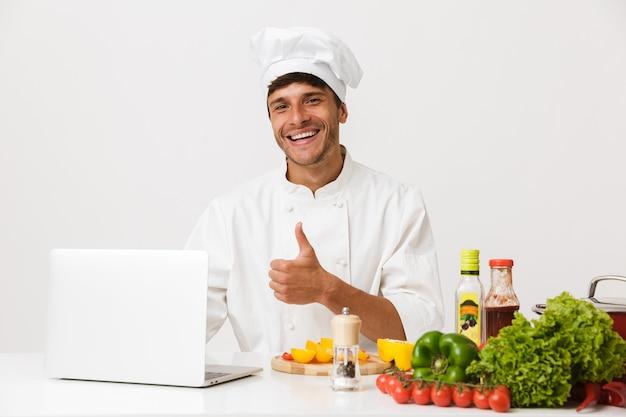L'uomo dello chef isolato sulla cucina bianca della parete fa i pollici sul gesto usando il computer portatile