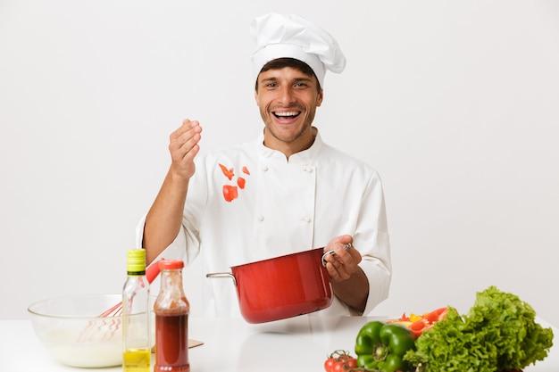 Uomo del cuoco unico isolato sulla cucina bianca della parete.