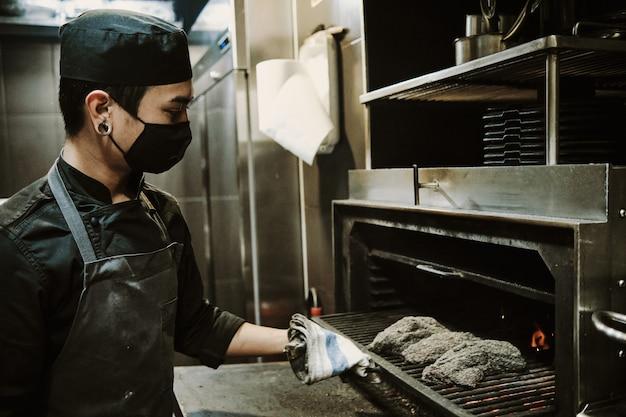Uomo del cuoco unico che mette il cibo nel forno alla cucina del ristorante.