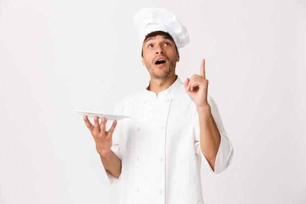 Chef uomo in piedi isolato sul muro bianco che punta a copyspace.
