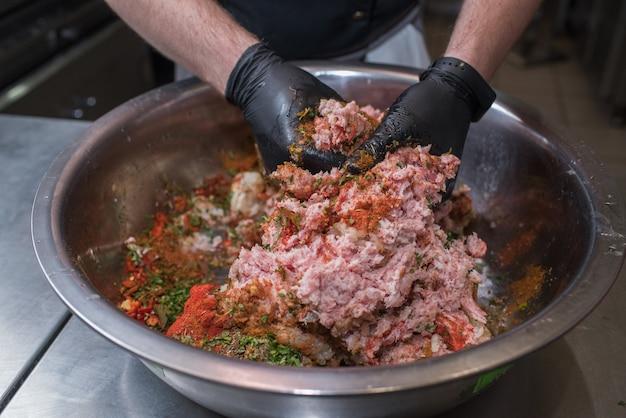 Lo chef mescola carne di maiale macinata con ingredienti diversi