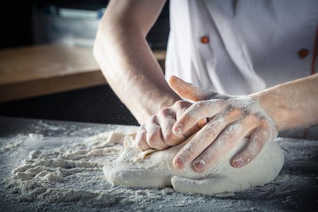 Lo chef prepara l'impasto con la farina. mani che impastano pasta cruda orizzontale. copia spazio. pasta senza glutine per pasta, pasticceria o pizza. posto di lavoro baker. lo chef produce un impasto. gastronomia, cucina, concetto di panetteria