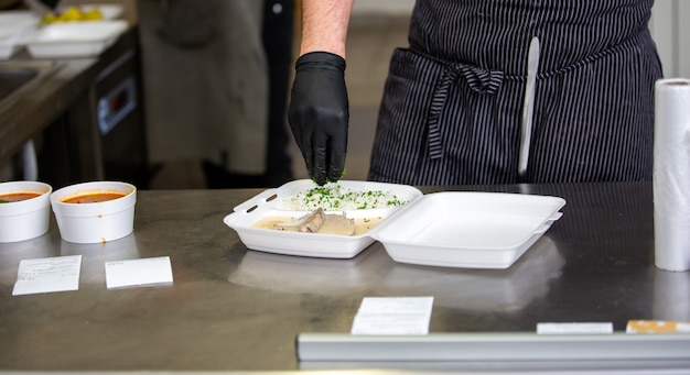Chef prepara il piatto in una scatola nel ristorante per il servizio di consegna di cibo a casa, ordinazione online