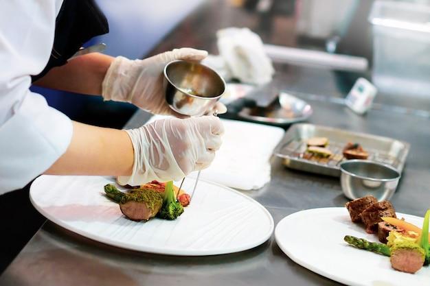 Cuoco unico che prepara cibo, pasto, in cucina, chef di cucina, piatto di decorazione del cuoco unico