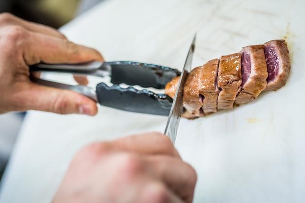 Lo chef prepara la presentazione di un piatto di filetto di maiale con purè di patate.