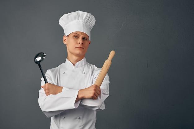 Chef professionista nel ristorante uniforme che cucina sfondo scuro dark