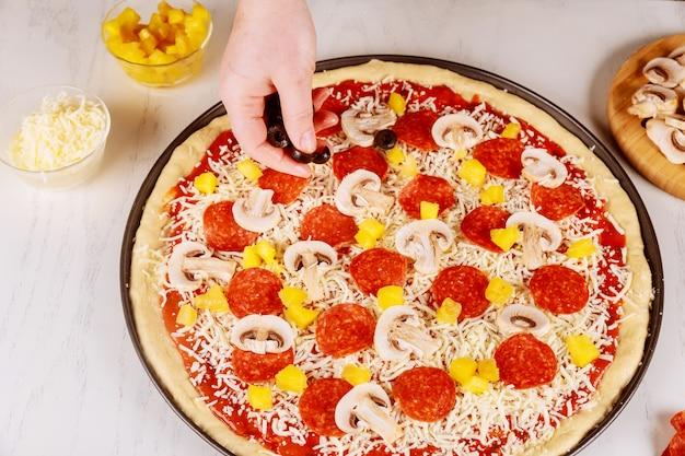 Lo chef mette olive sulla pizza cruda cruda.