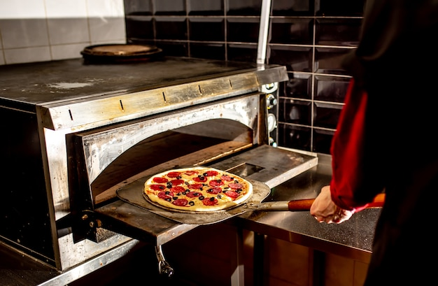 Chef mettendo la pizza in forno per cucinare