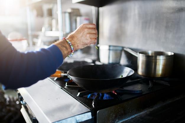 Chef in cucina del ristorante condimento cibo cucina nel wok