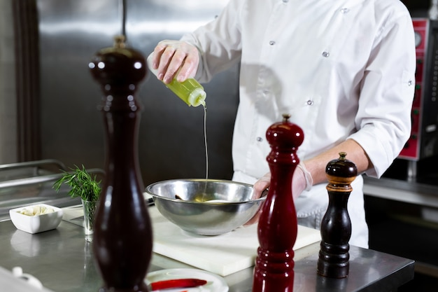 Lo chef del ristorante fa marinare i frutti di mare in una ciotola