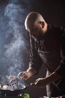 Lo chef arrostisce funghi di champagne su uno spiedino in crosta di formaggio.