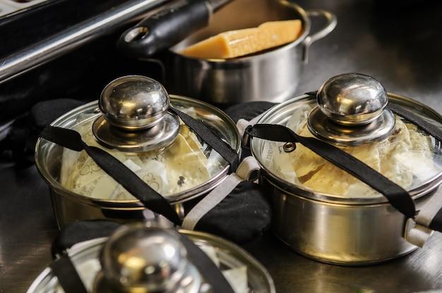 Le mani dello chef che confezionano il cibo nelle pentole nel ristorante automatico