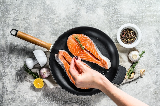 Lo chef salata trancio di salmone crudo in una padella. frutti di mare sani. muro grigio. vista dall'alto. spazio per il testo.
