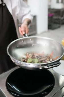 Chef che mette in mostra le sue capacità professionali. maestro di cucina al lavoro nella cucina del ristorante
