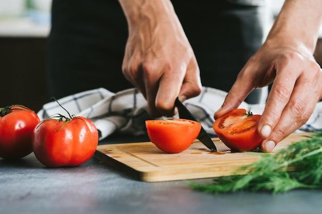Chef affettare il pomodoro usando il coltello sul tavolo in casa