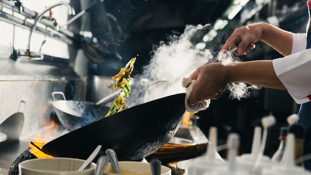 Lo chef friggere impegnato a cucinare in cucina. lo chef frigge il cibo in una padella, affumica e schizza la salsa in cucina.