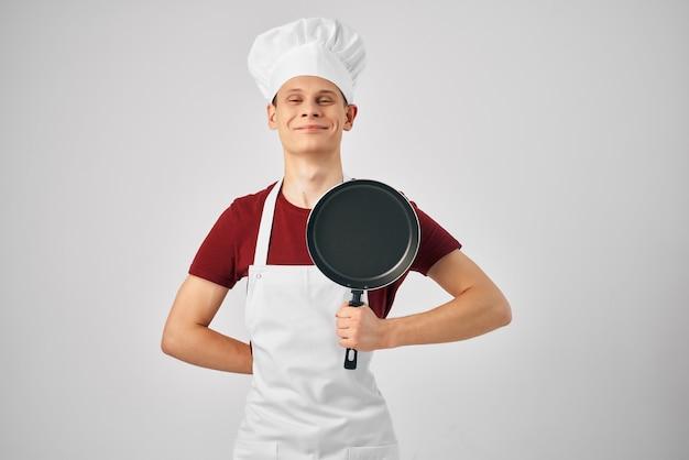 Chef in padella uniforme nelle mani di una cucina professionale del ristorante