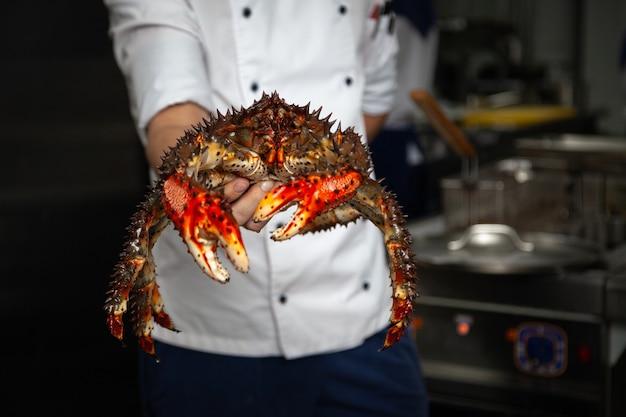 Lo chef in uniforme tiene il granchio in mano, si prepara a bollire