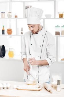Lo chef in uniforme fa l'impasto in cucina