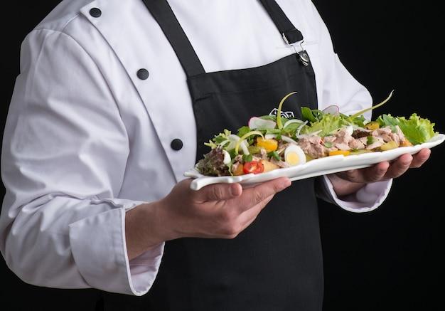 Lo chef in divisa serve un piatto in un piatto