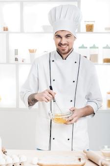 Chef in uniforme che monta uova e latte in una ciotola in cucina