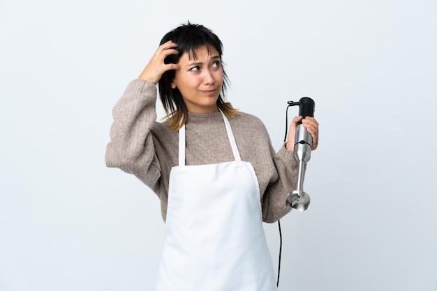 Ragazza uruguaiana del cuoco unico che usando il miscelatore della mano sopra la parete bianca che ha dubbi e con l'espressione confusa del fronte
