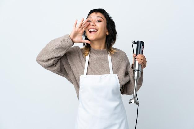 Ragazza uruguaiana del cuoco unico che usando il miscelatore della mano sopra la parete bianca che grida con la bocca spalancata