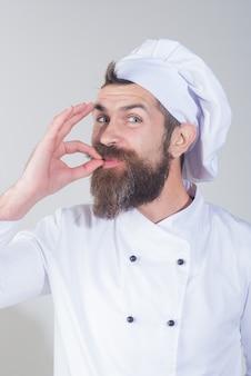 Lo chef in uniforme bianca mostra il segno della mano per la perfezione e l'eccellenza. uomo chef professionista che mostra il segno perfetto. professione, cucina, gesto e concetto di cibo - lo chef maschio felice mostra un gesto delizioso
