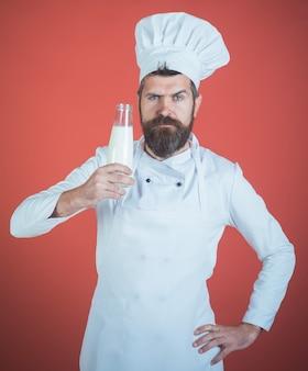 Lo chef con la faccia sicura in uniforme bianca presenta la migliore bevanda al latte è l'uomo del latte con la barba e