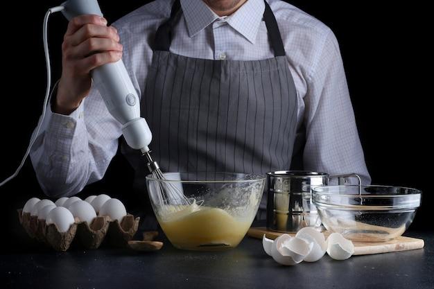 Chef con mixer in mani che cucinano torta con ingredienti sul tavolo