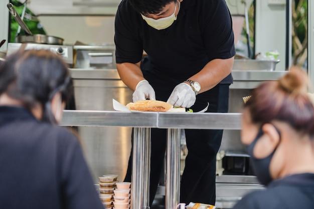Chef con maschera protettiva che prepara panino sul camion di cibo.