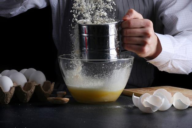 Chef con setacciare in mani che cucinano torta con ingredienti sul tavolo