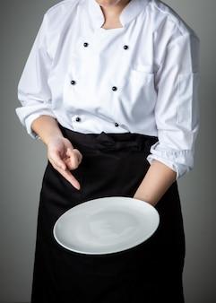 Chef con piatto vuoto bianco