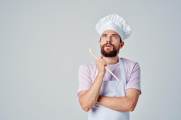 Chef con cucchiaio di legno in mano che lavora in cucina professionale