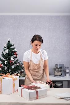 Chef donna in grembiule con confezione regalo in cucina su sfondo albero di natale. cornice verticale.